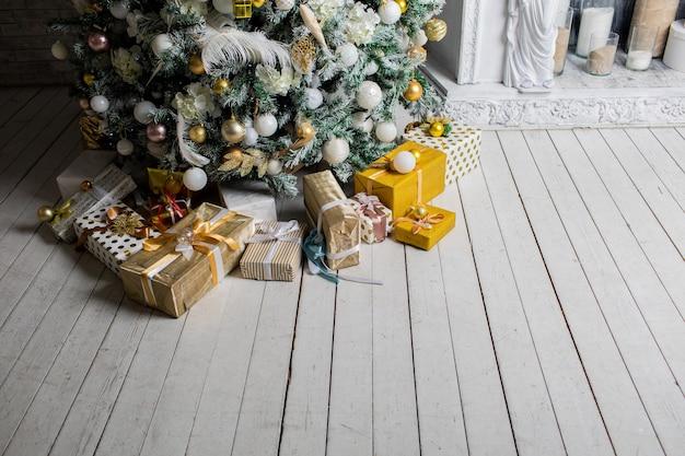 Cadeau de vacances sous le sapin de noël emballé avec de la ficelle et du papier d'emballage décoré de guirlandes et de jouets.