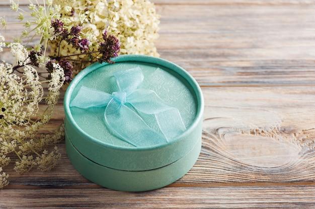Cadeau vert min à la main avec noeud, fleur