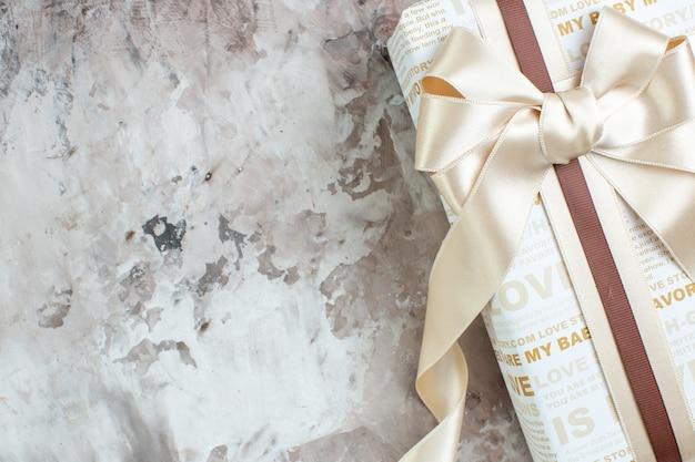 Cadeau vue de dessus attaché avec un ruban blanc sur une table grise