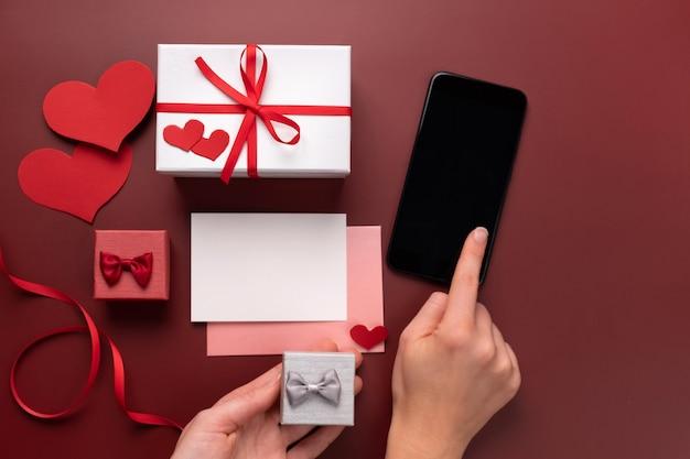 Cadeaux d'achat en ligne de la saint-valentin dans des boîtes. recherchez des cadeaux sur votre smartphone. copiez l'espace pour le message d'amour.
