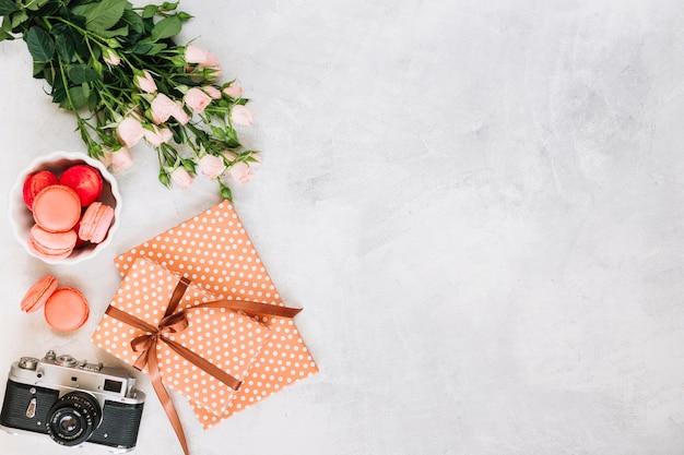 Cadeaux et appareil photo près de macarons et bouquet