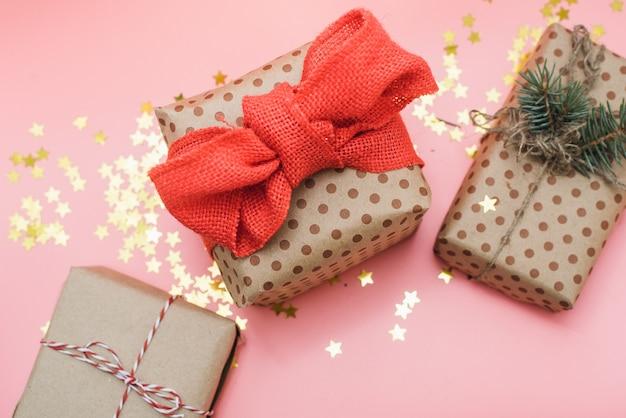 Cadeaux artisanaux avec un arc rouge sur pastel rose avec des confettis d'or