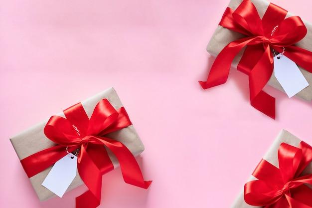 Cadeaux attachés avec un ruban rouge. saint valentin, noël, fête des mères, cadeaux d'anniversaire. concept de carte de voeux