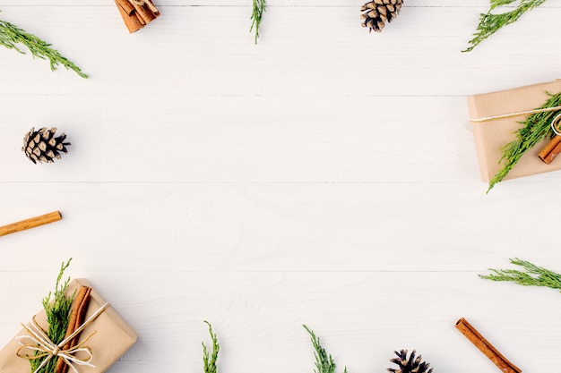 Les cadeaux et les branches de sapin forment un cadre vierge pour une carte de noël. vue de dessus.