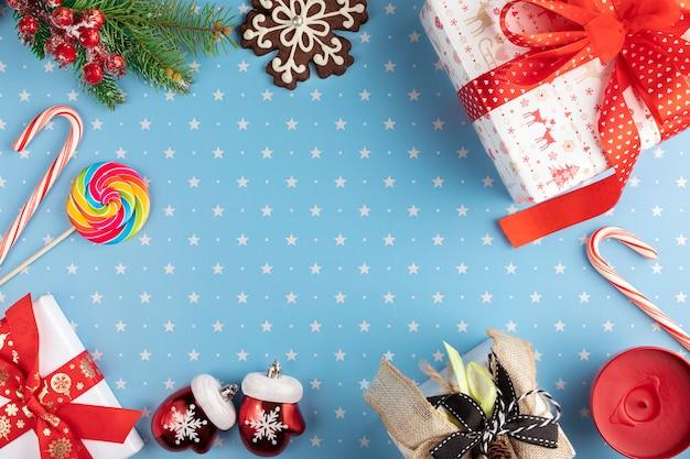 Cadeaux, branches de sapin avec fruits rouges, pain d'épice de flocon de neige et bonbons sur fond bleu avec motif d'étoiles .. noël, hiver, concept de nouvel an.