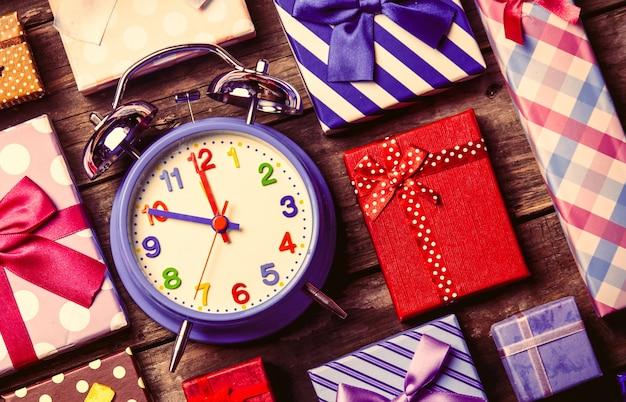 Cadeaux colorés et horloge bleue sur la table en bois marron