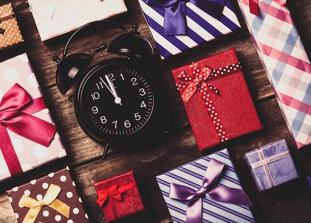 Cadeaux colorés et horloge noire sur la table en bois marron