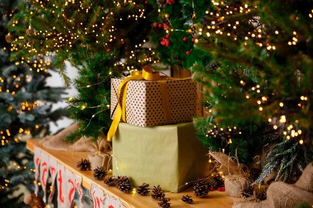 Cadeaux dans des boîtes en emballage artisanal se tiennent près de l'arbre du nouvel an sur une table en bois marron