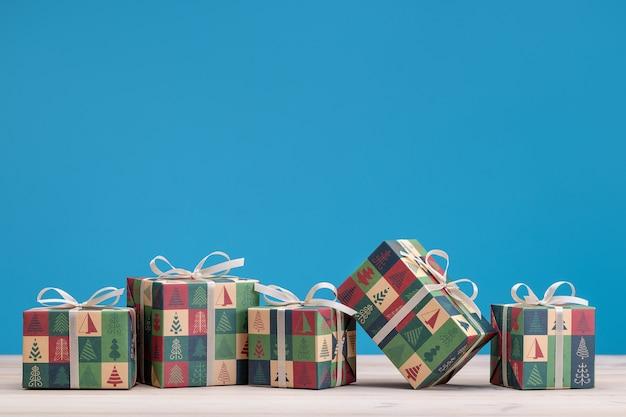 Cadeaux dans des boîtes, emballés dans du papier avec des dessins de noël et du nouvel an. copiez l'espace, fond bleu.