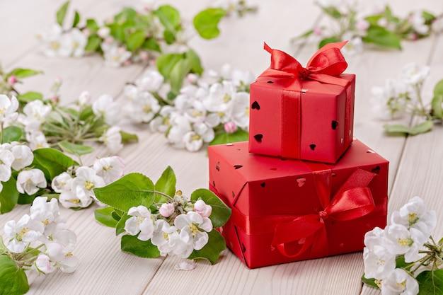 Cadeaux dans des boîtes rouges avec des rubans et des arcs. fleurs blanches de pommier.