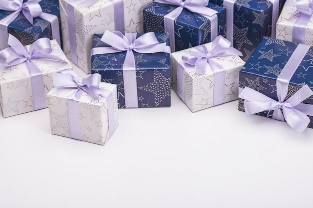 Cadeaux dans un emballage festif, avec des rubans, des arcs et des flocons de neige en bois sur un espace blanc.