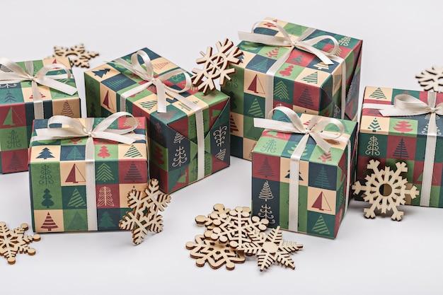 Cadeaux dans un emballage festif, avec des rubans, des nœuds et des flocons de neige en bois