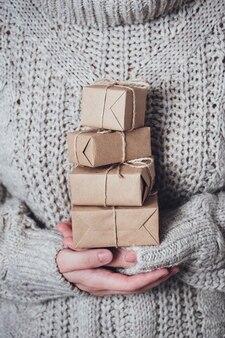 Cadeaux dans les mains des femmes, gros plan. concept de cadeau monochrome et minimaliste. une fille en pull tient des coffrets cadeaux en papier kraft, attachés avec une ficelle. fond de surprise, carte de voeux.