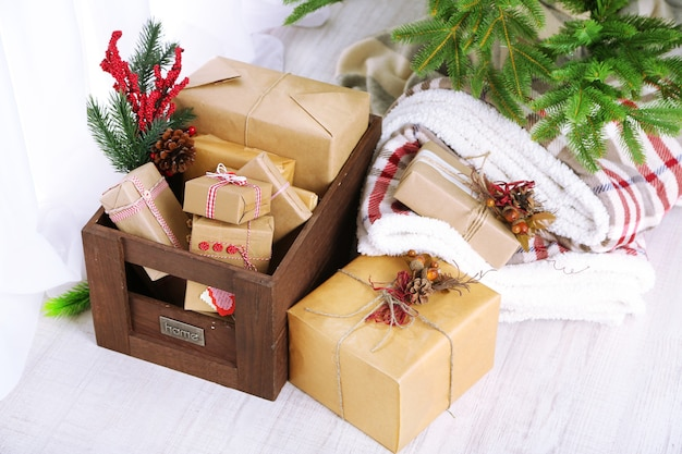 Cadeaux et décorations de noël dans des boîtes près de l'arbre de noël sur fond clair