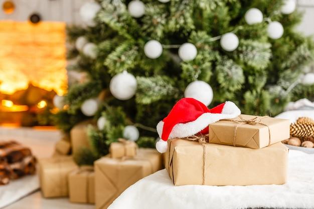 Cadeaux du nouvel an sous le sapin de noël. les cadeaux sont emballés dans du papier kraft et liés