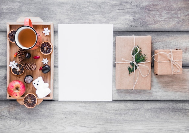 Des cadeaux et du thé près de la feuille de papier