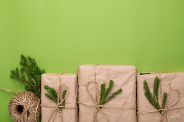 Cadeaux écologiques avec des plantes vertes en papier kraft sur une surface verte