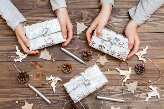Cadeaux emballés dans du papier de fête dans les mains des enfants et des décorations de noël sur un fond en bois. préparations de noël