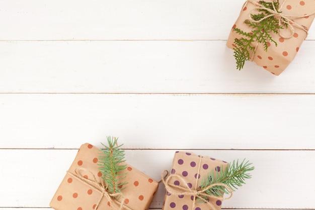 Cadeaux emballés avec du papier kraft sur une table en bois blanche