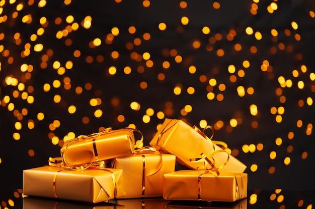 Cadeaux emballés sur fond de bokeh de lumières dorées