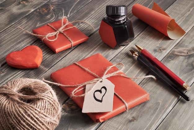 Cadeaux emballés, papier, cordon et étiquettes sur une table en bois marron