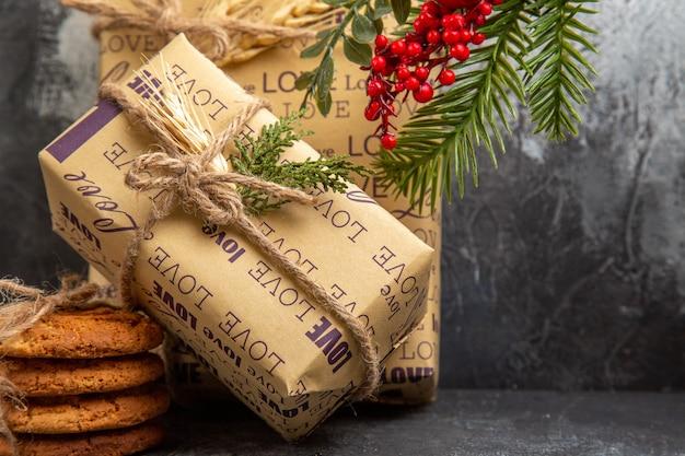Cadeaux emballés pour les membres de la famille debout sur le mur et biscuits empilés sur fond sombre