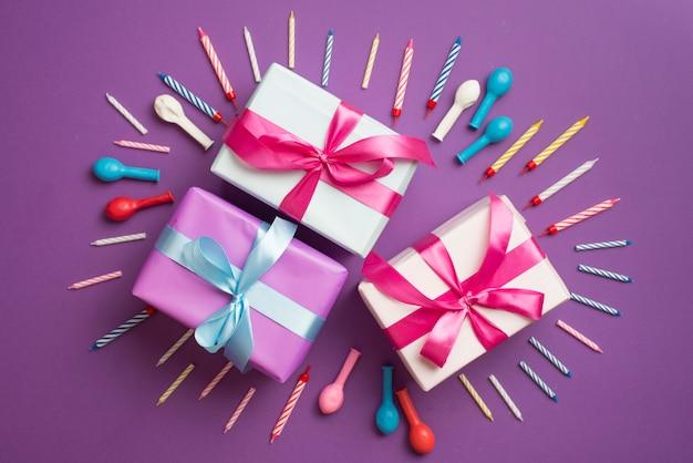 Cadeaux entourés de bougies et de ballons