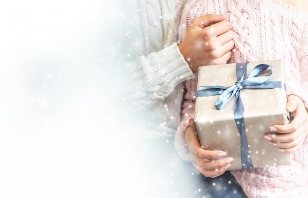 Cadeaux entre les mains d'un homme et d'une femme, mise au point sélective.
