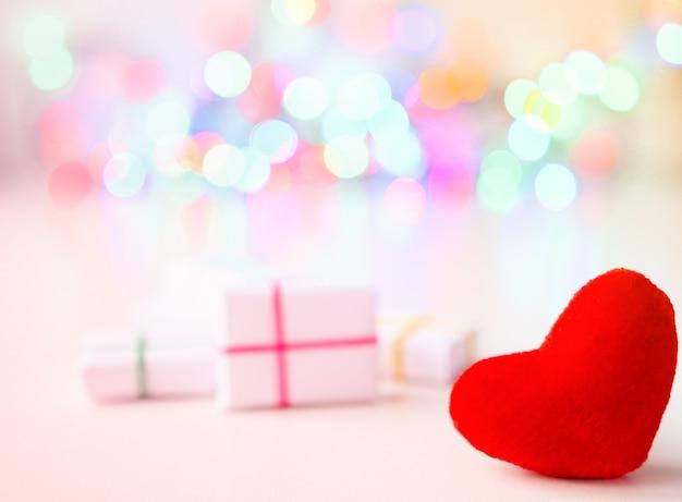 Cadeaux enveloppés de coeur textile rouge sur fond blanc avec lumière de défocalisation