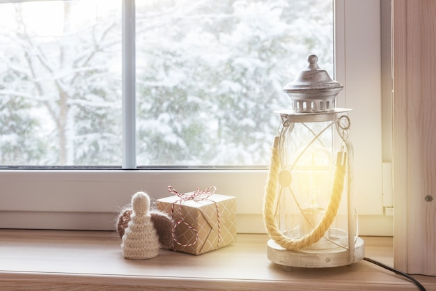 Cadeaux festifs de lanterne de noël et ange sur un rebord de fenêtre en bois en hiver à l'intérieur