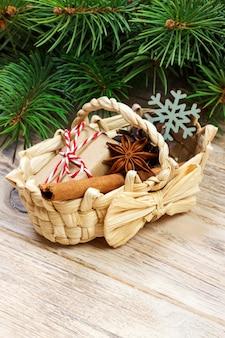 Cadeaux de fête avec boîtes, anice étoilée, panier, cannelle et flocon de neige sur bois