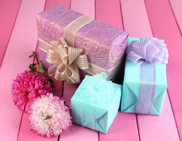 Cadeaux et fleurs, sur fond de bois clair
