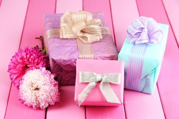 Cadeaux et fleurs, sur une surface en bois clair