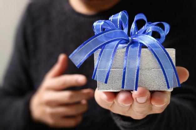 Cadeaux, main d'homme tenant une boîte-cadeau dans un geste de générosité