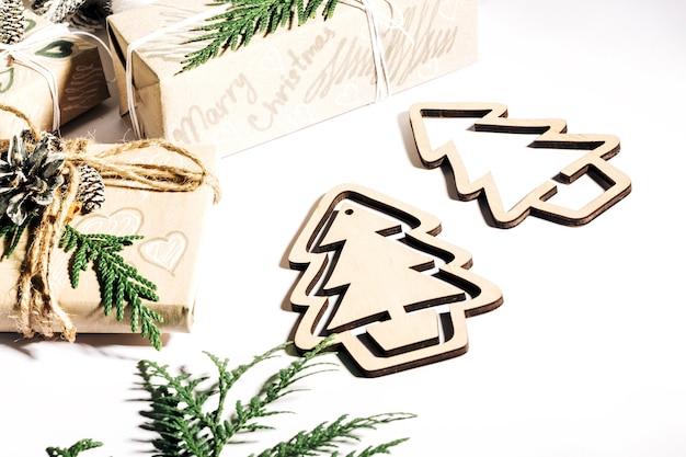 Cadeaux de noël avec boîte-cadeau décorée de pommes de pin et de brindilles sur fond blanc, préparation pour les vacances.
