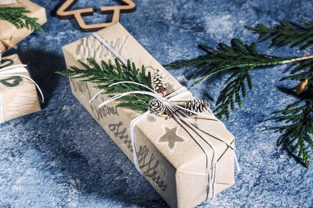 Cadeaux de noël avec boîte-cadeau décorée de pommes de pin et de brindilles