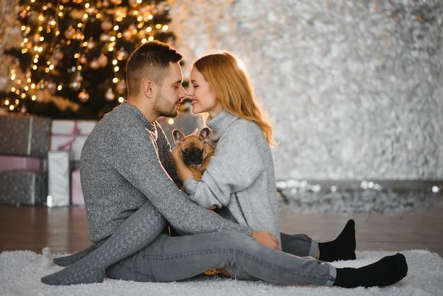 Cadeaux de noël et bonheur entre un jeune couple et un chien mignon