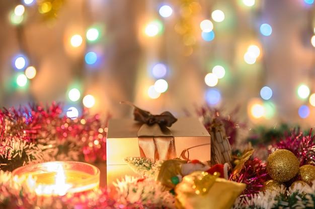 Cadeaux de noël et une bougie décorée de guirlandes sur le fond d'une guirlande étincelante.