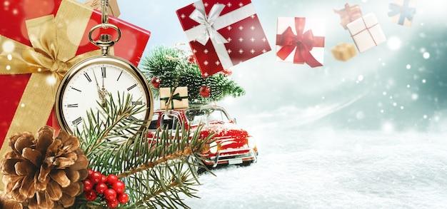 Cadeaux de noël ou cadeaux du nouvel an sur fond neigeux. petite voiture transportant un arbre de noël sur un toit. montre de poche du nouvel an avec branches de sapin et pomme de pin. carte de vacances de noël, bannière web.
