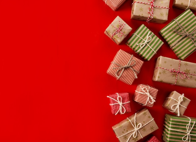 Cadeaux de noël cadeaux sur fond rouge. coffrets cadeaux simples et classiques emballés en rouge et blanc avec des nœuds en ruban et des décorations de vacances