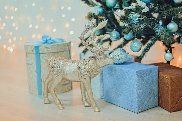 Cadeaux de noël et cerf-jouet sous le sapin de noël en bleu.