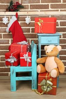 Cadeaux de noël sur chaise et bibliothèque sur mur de briques brunes