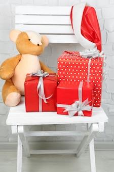 Cadeaux de noël sur une chaise blanche sur fond de mur de brique