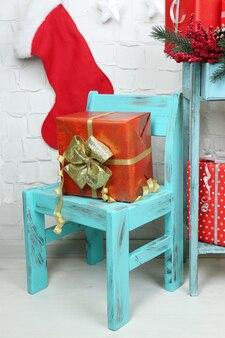 Cadeaux de noël sur chaise bleue sur fond de mur de brique