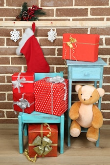 Cadeaux de noël sur chaise sur fond de mur de briques brunes