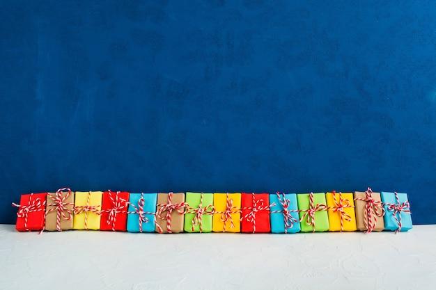 Cadeaux de noël colorés dans une rangée sur fond bleu avec espace de copie