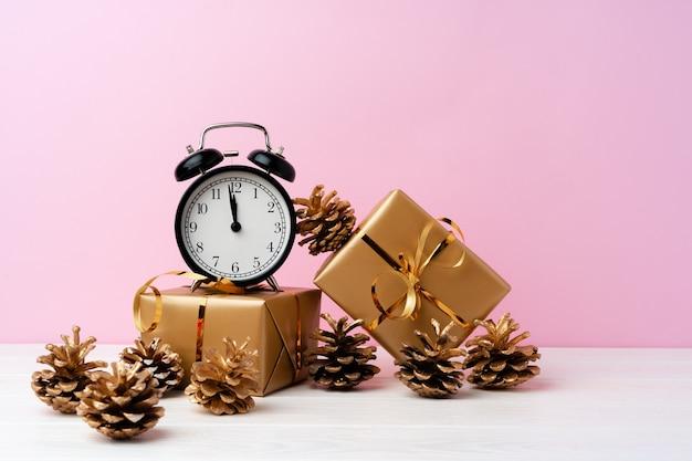 Cadeaux de noël, cônes et réveil contre rose