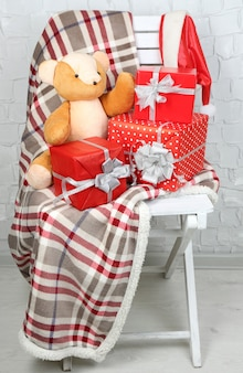 Cadeaux de noël sur une couverture sur une chaise blanche sur un mur de briques