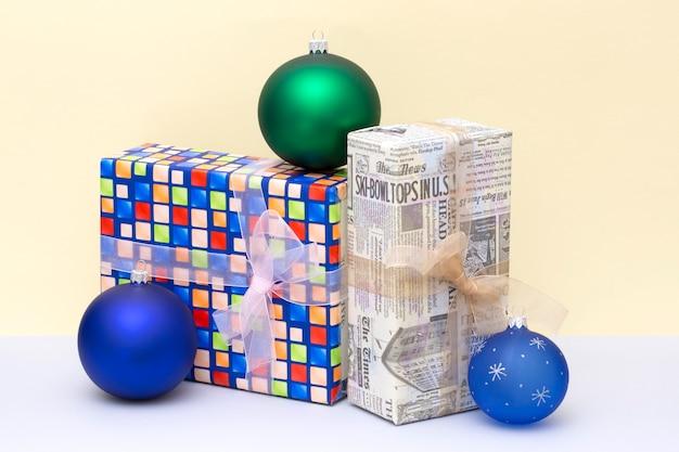 Cadeaux de noël dans des boîtes et des boules de noël sur un fond coloré