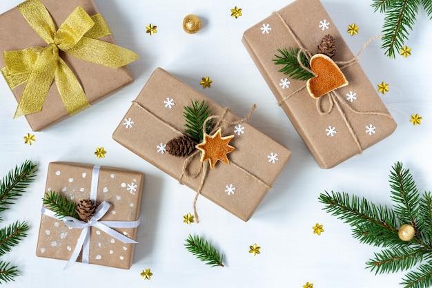 Cadeaux de noël dans un décor de fête avec de la ficelle écologique et des arcs de ruban à côté de branches de sapin sur tableau blanc